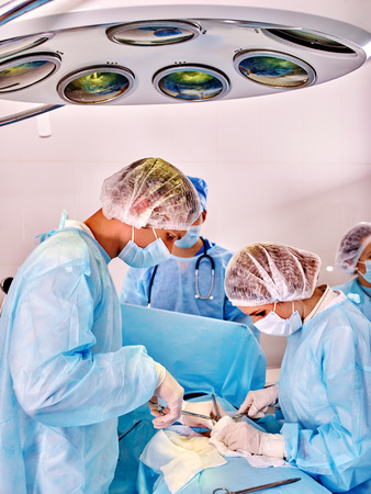 surgery stretcher: Sick patient and group doctors in operating room. Surgeons operate.