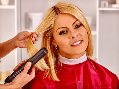 hair curler: Happy blonde woman at hairdresser with iron hair curler.