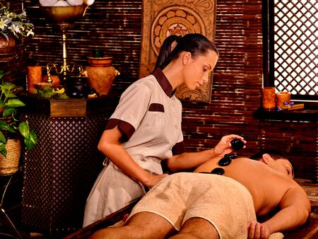 lastone: Man  having oil Ayurveda spa lastone treatment. Stock Photo