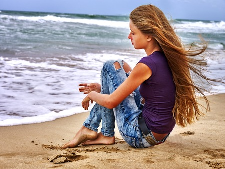 Summer girl sea.  Young girl sitting and dreams on coast near ocean with waves.