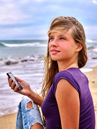 first love: Girl call mobile phone on sand near sea. First love.