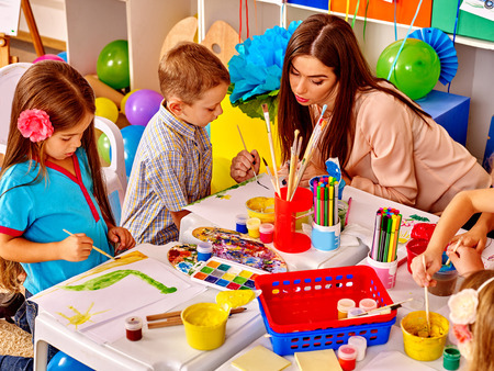 children painting: Two children with female teacher painting  in  kindergarten .