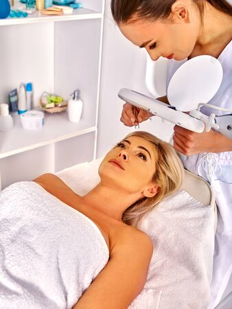 tweezing eyebrow: Woman middle-aged have procedure tweezing eyebrow in spa salon with young beautician. Stock Photo