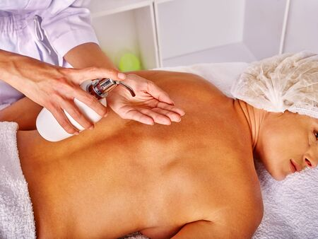 antiaging: Woman middle-aged take back massage with cosmetics in spa salon with young beautician.
