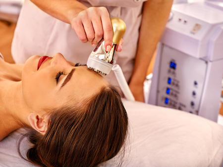 Young happy woman receiving electroporation  facial gold therapy at beauty salon. Stock Photo