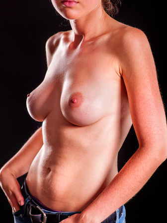 breast examination: Body of a girl with beautiful naked breasts in jeans. Stock Photo
