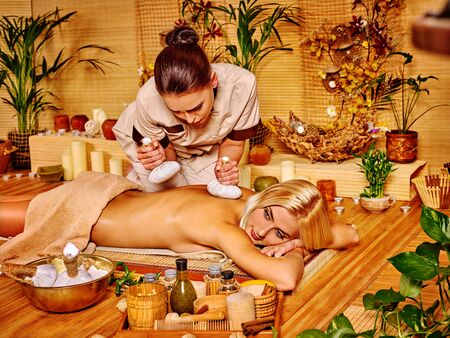 relax massage: Blond woman getting massage relax in tropical wooden  spa.