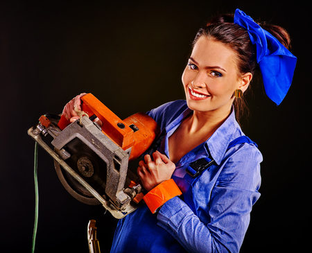 circular saw: Happy woman in builder clothers holding circular saw. Fashion concept.