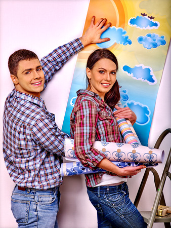 redecoration: Happy husband and wife glues wallpaper at home. Stock Photo