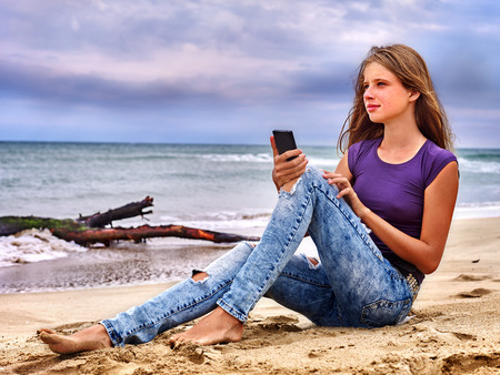 Girl with mobile phone make selfie on sand near sea. Stock Photo