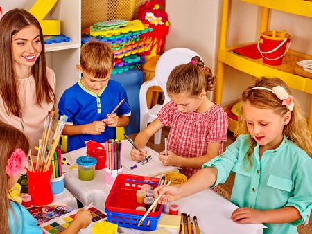 kinder: Los niños del grupo con la mujer del profesor learnig pintura sobre papel en el kinder.