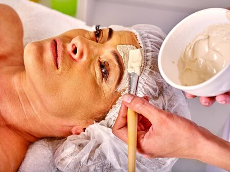 antiaging: Woman middle-aged take facial and neck clay anti-aging mask in spa salon. Stock Photo