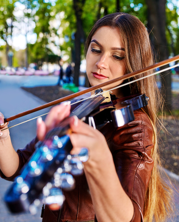 improvisation: Music street performers girl violinist  playing  in park.