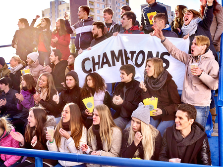 grandstand: Sport fans holding banner with writting champion and singing on tribunes. Group people. Stock Photo