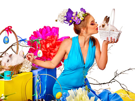 female animal: Fashion woman  holding flowers in easter style kissing bunny . Isolated.