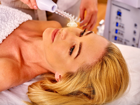 devices: Young beautiful woman looking up receiving electric darsonval facial massage after procedure at beauty salon. Stock Photo