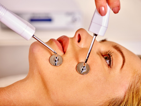 Young woman receiving electric galvanic anti-aging face spa massage at beauty salon.