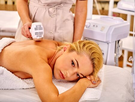 rf: Young upset woman receiving electric back massage on microdermabrasion equipment at beauty salon.