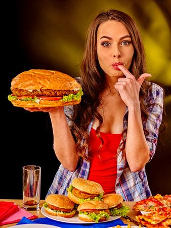 fastfood: Cô gái hương vị fastfood bánh hamburger lớn và pizza.