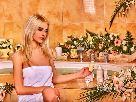 luxuriate: Young blond woman luxuriate at flowers water spa.