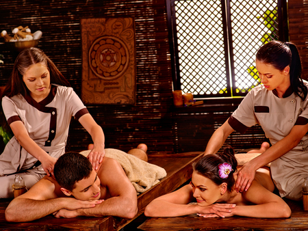 luxuriate: Loving couple  luxuriate  at oil Ayurveda spa treatment on wooden bed. Stock Photo