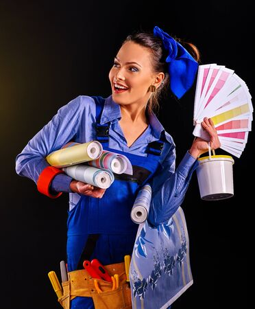 female construction worker: Builder woman holding roll wallpaper and tin of paint on black background.