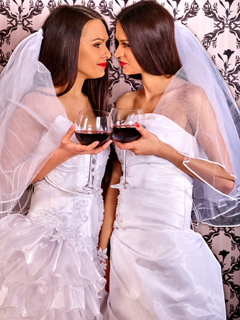 adult nude: Wedding lesbians girl wearing white long bridal dress drinking red wine. Wallpaper background.