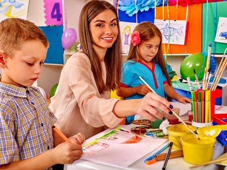 preescolar: Los ni�os con el profesor de pintura femenina en el papel de la pintura y l�pices en la guarder�a. Foto de archivo