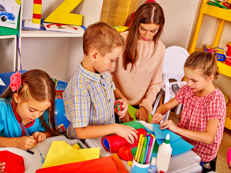 children painting: Children with female teacher learning painting on paper  in  kindergarten .