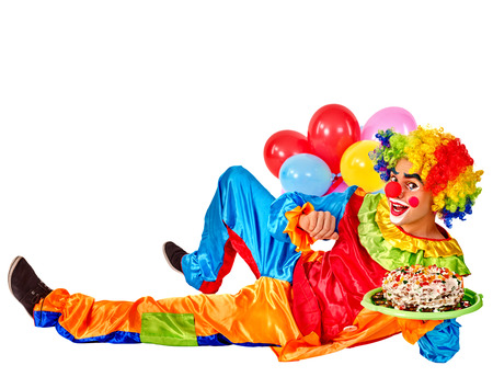 adult birthday party: Happy birthday clown holding cakes and bunch of balloons lying on floor.  Isolated. Stock Photo