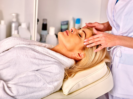 Woman middle-aged in eyes closed take face and neck massage in spa salon. Imagens
