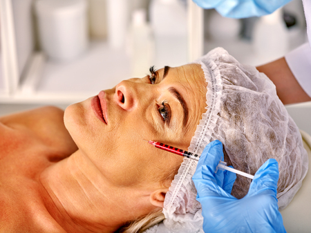 35 40 years old: Woman middle-aged  looking up in spa salon giving injections.