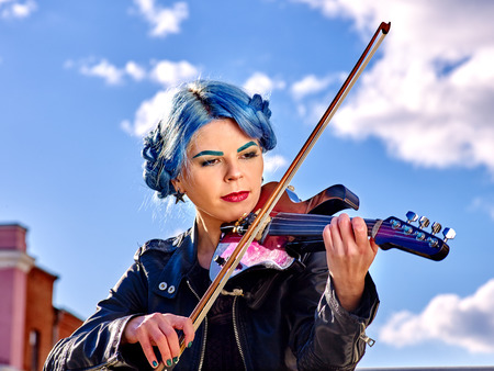 solitariness: Girl violinist with blue hair playing  aganist sky with clouds outdoor. Stock Photo