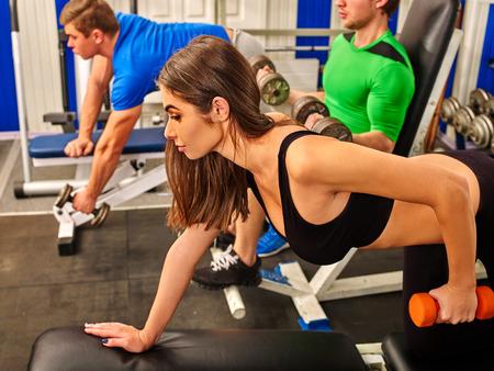 Grupo de personas hombres y mujeres Harding trabajo con pesas en el gimnasio de su cuerpo.