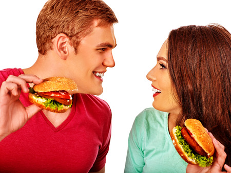 red food: Young couple man and woman flirting and eating hamburgers  . Fastfood concept.  Isolated. Stock Photo