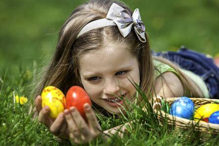 girl lying: Happy little girl  look for easter egg outdoor. Girl lying on green grass. Stock Photo