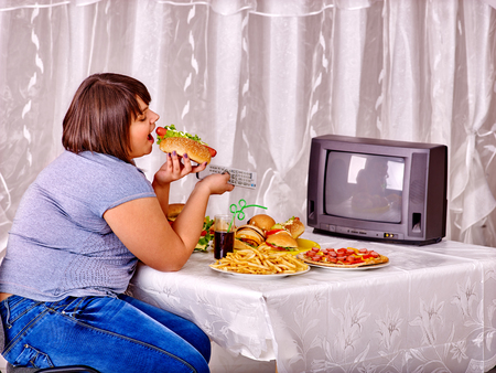 beefburger: Overweight woman eating fast food and watching TV. Concept junk.