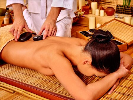 stone therapy: Woman getting stone therapy massage on bamboo floor spa. Stock Photo