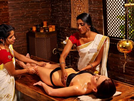 panchakarma: Woman having exotic massage with pouch of rice to India spa salon.