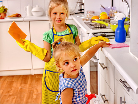 dish washing gloves: Children wash dishes and furniture in kitchen. Stock Photo