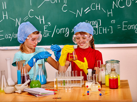 chemistry class: Happy children holding flask do experiments in chemistry class.