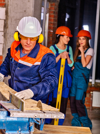 hearing protection: group people  builder hard working with circular saw.