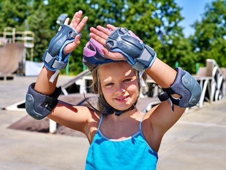 inline skater: Girl wearing helmet riding on roller skates in skatepark.