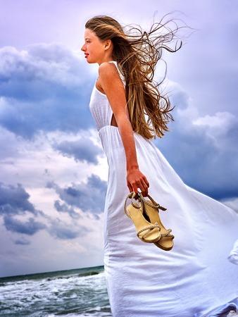 viento: Mar Chica de verano. Mujer con zapatos en las manos pasando costa. Foto de archivo