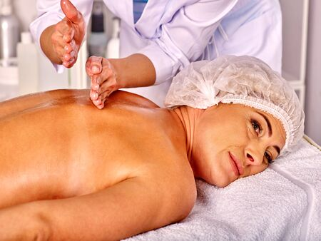 age 35 40 years: Woman middle-aged wearing cosmetic hat  take back massage in spa salon with young beautician.