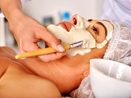 35 40 years old: Woman middle-aged take facial and neck clay mask in spa salon. Seen female hands
