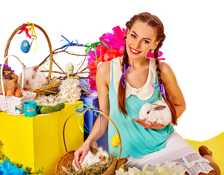 animal sexy: Young beautiful woman in easter style holding eggs and group of bunny in basket.
