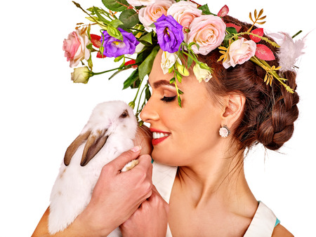 Fashion woman in easter style kissing white bunny and flowers. Isolated.