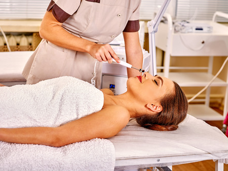 electrophoresis: Woman receiving electric galvanic antiaging face medical massage at beauty salon. Stock Photo