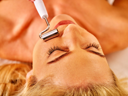 massager: Young woman with closed eyes receiving electric galvanic face spa massage at beauty salon.
